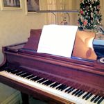 Cherry piano with bronze lamp